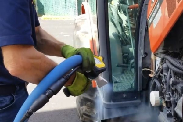 A person cleaning and repairing a truck