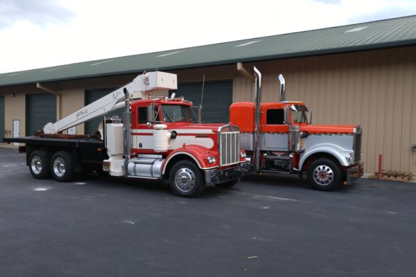 Two red trucks in front of a storage facility