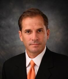 Portrait of a man wearing a suit and orange tie