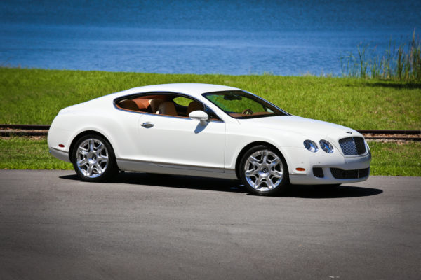 A white luxury car parked near the ocean