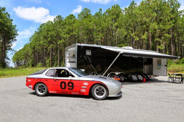 A classic race car parked near a trailer