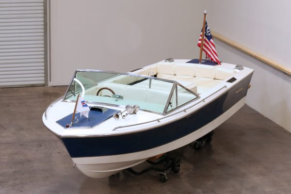 A white and blue boat in a storage facility