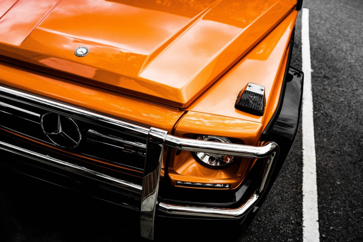 The hood of a shiny orange car